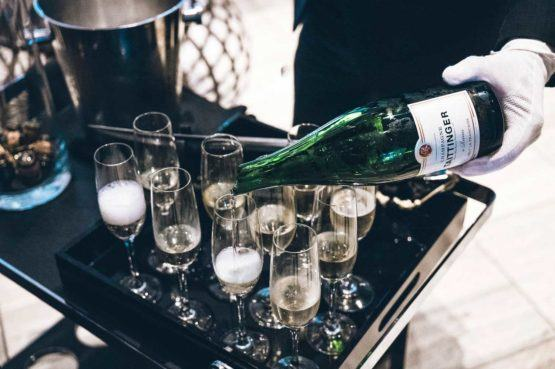a waiter wearing white gloves pouring champagne into 10 glasses